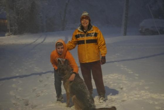German shepherd in snow in the light of a streetlight with a boy in a University of Tennessee Hoodie (I know. Hoodie in the snow, but it's his fault if he gets cold), and a woman in yellow coat smiling at camera
